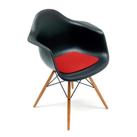 Lateral single image of the Eames Plastic Armchair in black with the felt cushion in red by Hey Sign.