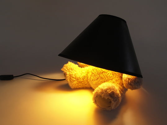 The Teddy Bear LED Lamp from Suck UK is a table lamp with a lamp shade on top of a teddy bear, concealing its head. A perfect lamp for creating a very warm and soft light.