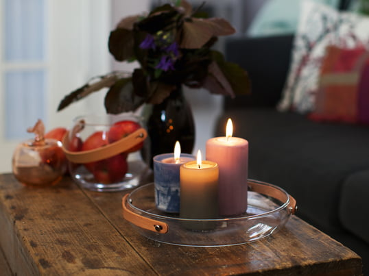 The Design with light candle plate by Holmegaard emphasises the cozy atmosphere created by the colorful candles and their warm light. The leather handle of the design decoration highlights the comforting mood.