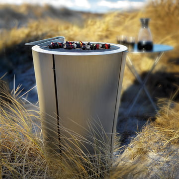 Eva Solo Barrel Grill with food on grid and tongs on beach