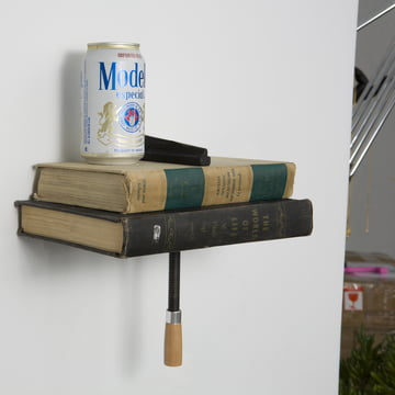 The Wall Clamp Shelf with books and a can